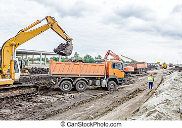 Excavator is loading a truck on building site