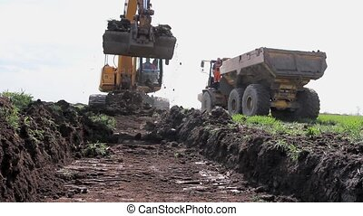 Excavator is loading a truck with ground on building site -...