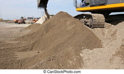 Excavator is preparing pile of sand for loading in truck on...