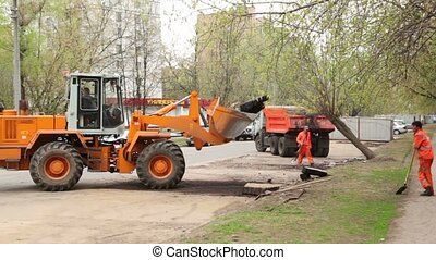 Excavator lifts asphalt, workers stand near at dismantling of small garages