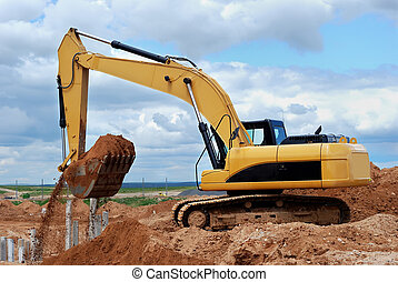 Excavator loader at construction site with sand in bucket...