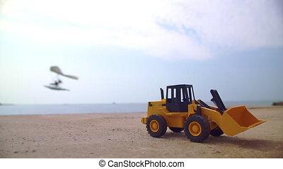 Excavator loader model standing on sand with a glider flying...