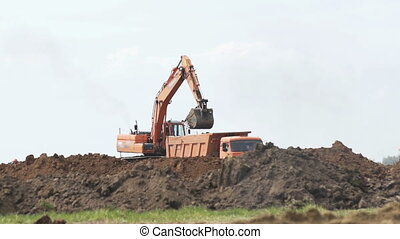 Excavator loading a transportation truck on construction...