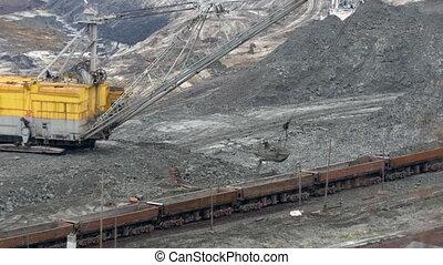 Excavator loading of iron ore on train. 4K UltraHD video