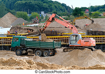 Excavator loads the ground in the truck