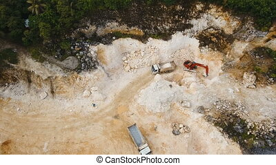 Excavator loads truck in quarry. Philippines,Siargao.