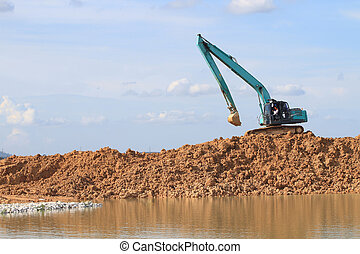 Excavator located by a river and ready for work