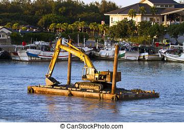 excavator machine construct on sea - A large yellow...