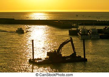 excavator machine construct on sea under twilight - A large...