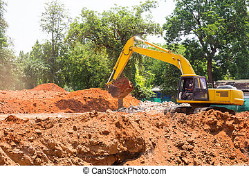Excavator on mound and tree background