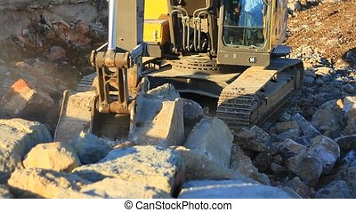Excavator operating in a rock quarry. Hydraulic excavator works for formation of new land.