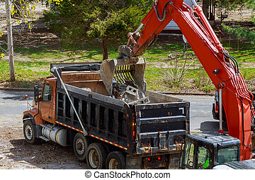 Excavator picks up construction waste for loading onto a truck