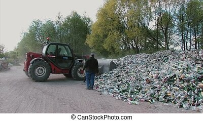 Excavator removes trash paper and plastic bottles for recycling