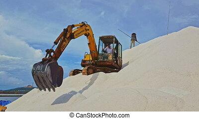 Excavator Stands on Salt Heap Pours Salt Upward with Scoop