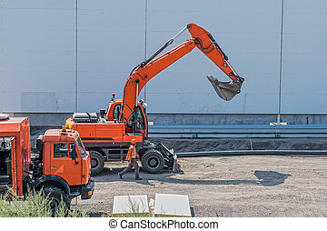 Excavator, truck and foreman at construction site