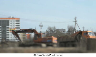 Excavator uploads a clay in a truck using a bucket