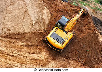 Excavator working on a heap of sand