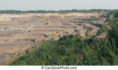 Excavators and heavy trucks in the quarry mining granite