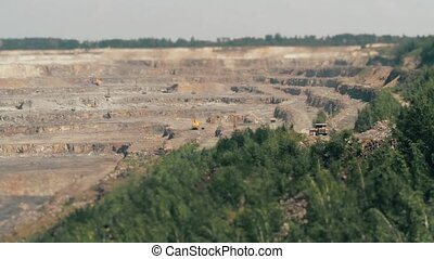 Excavators and heavy trucks in the quarry mining granite TILT-SHIFT