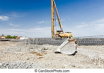 Excavator's bucket and shovel in front of skeleton reinforcing steel, armature, bar at construction site.