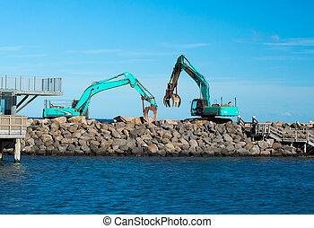 Excavators working near the sea