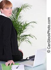 Exceeded businesswoman sitting on her desk