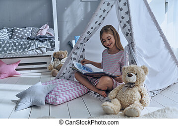 Excellent book. Cute little girl reading book while sitting...