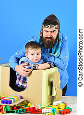 Excessive care. Annoyed child and tricky father on blue background with constructor and cardboard plane. Young model in professional studio. Bearded man in pilot hat and goggles hugs little boy.