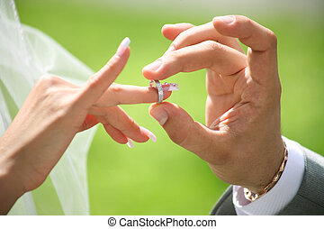 Close-up of groom?s hand putting wedding ring on bride?s finger