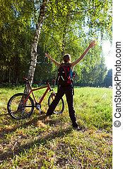 excitado, joven, ciclista, posición, en, un, primavera, parque, con, manos, outstretched., soleado, al aire libre