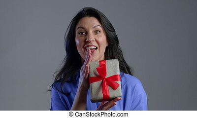 Excited adult woman received gift box with bow. She is happy and flattered by attention. Mature lady dancing with present on grey background. Studio footage. 4k