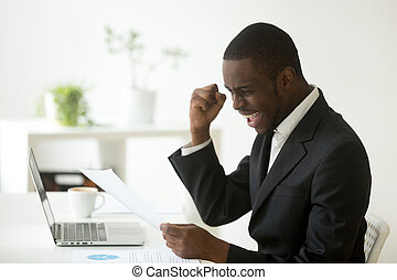 Excited african american businessman reading letter with unexpec