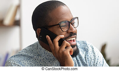 Excited African American businessman talking on phone at workplace