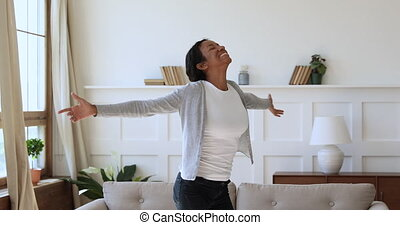 Excited african woman spinning with arms outstretched in new apartment