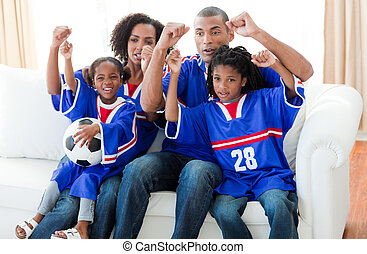 Excited Afro-American family watching a football match