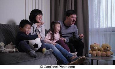 Excited asian family watching football match on TV - Happy ...