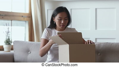 Excited asian female consumer opening parcel box receiving shipment order