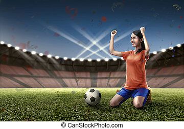 Excited asian female football player celebrate her victory
