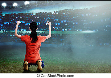 Excited asian football player woman with happy expression