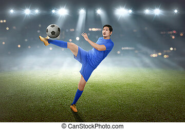 Excited asian footballer showing his skill