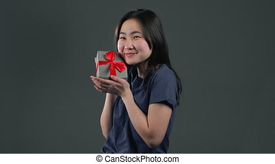 Excited asian girl received gift box with bow. She is happy and flattered by attention. Korean girl on grey background. Studio footage