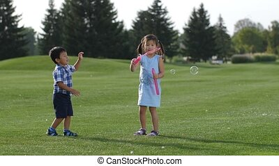 Excited asian siblings having fun with soap bubbles