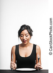 Excited asian woman sitting at the table