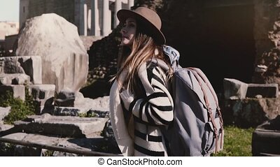 Excited attractive young female tourist with backpack in stylish hat exploring the Forum in Rome looking around smiling.