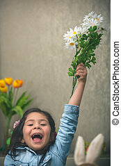Excited baby girl with flowers