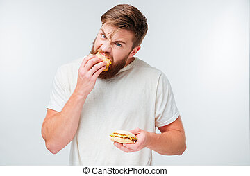 Excited bearded man greedily eating hamburgers