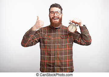 Excited bearded man is showing thumb up and an alarm clock.