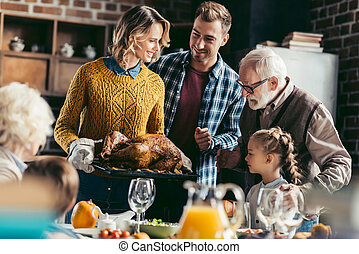 family looking at thanksgiving turkey