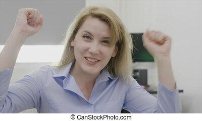 Excited beautiful female entrepreneur raising arms happy and confident for her success and victory business achievement