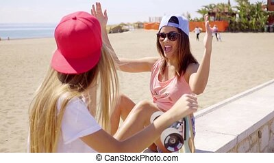 Excited beautiful skater friends near beach wearing...